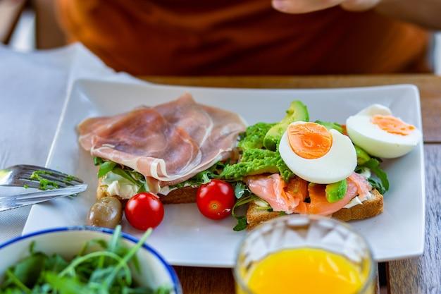 Eiertoast toast mit schinken zum frühstücksommerfrühstück auf der terrasse draufsichtfamilienpause