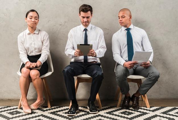 Eifersüchtige geschäftsfrau, die nahe dem geschäftsmann unter verwendung der digitalen tablette sitzt