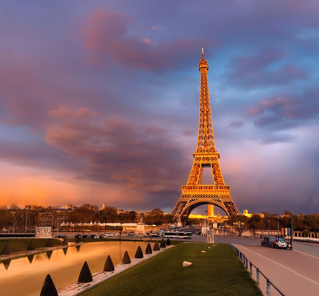 Eiffelturm auf einem sonnenuntergang halb beleuchtet mit den letzten strahlen der untergehenden sonne
