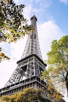 Eiffelturm im grün der bäume gegen den blauen himmel. vertikal.