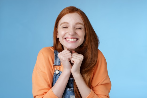 Eifrige freude begeistert hübsches junges rothaariges mädchen schließen augen träumerisch lächeln erhalten großartiges ergebnis gelehrterchip triumphierend freudig grinsend squeez hände aufgeregt stehend blauen hintergrund sehr glücklich