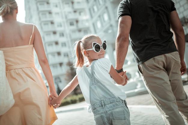 Eigener stil. kleines lächelndes mädchen, das lustige große sonnenbrillen auf dem spaziergang trägt und händchen mit ihren eltern hält