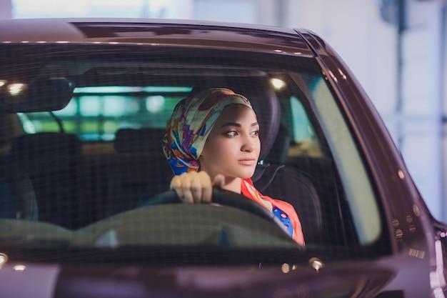Eigentums- und personenkonzept - muslimische frau im hijab mit autoschlüssel über auto zeigen hintergrund. glückliche frau, die autoschlüssel vom händler in der autoausstellung oder im salon nimmt