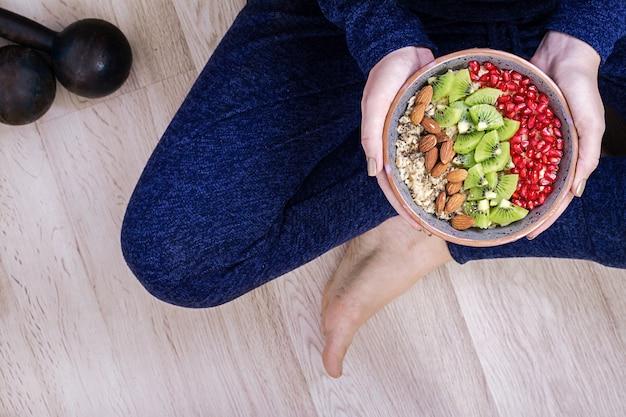 Eignung und gesundes lebensstilkonzept. frau steht still und isst ein gesundes hafermehl