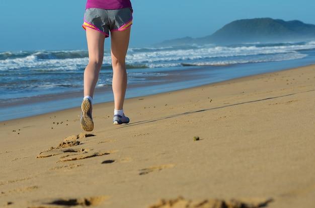 Eignung und laufen auf strand, frauenläuferbeinen in den schuhen auf sand nahe meer, gesundem lebensstil und sportkonzept