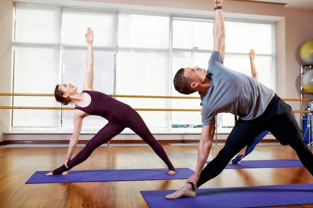 Eignung, yoga und gesundes lebensstilkonzept - eine gruppe von personen, die übungen für das ausdehnen und das meditieren in den verschiedenen yogahaltungen tun.