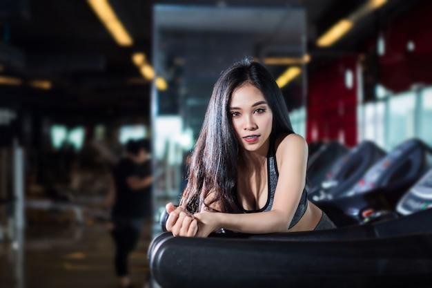 Eignungs-asiatinnen, die übungen tuend durchführen, den lauf auf tretmühle ausbilden