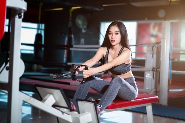 Eignungs-asiatinnen, die übungen tuend mit rudermaschine in der sportgymnastik durchführen