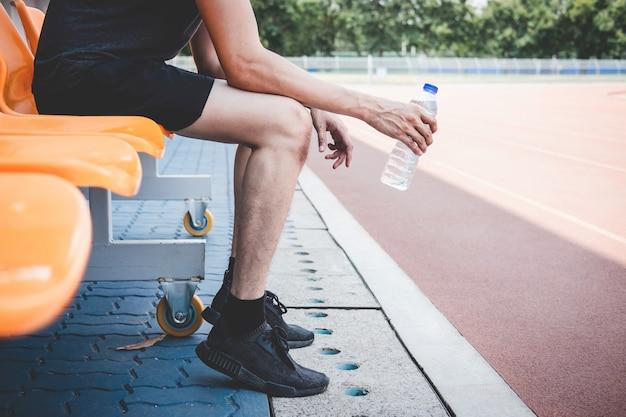 Eignungsathletenmann, der auf bank mit der flasche wasser sich vorbereitet, auf straßenbahn zu laufen stillsteht