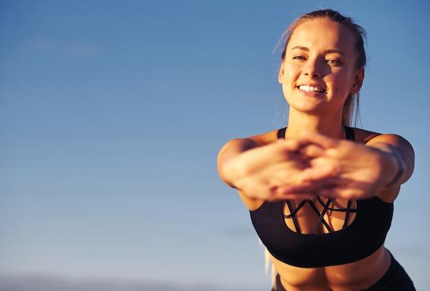 Eignungsfrau, die hände auf hintergrund des blauen himmels ausdehnt. nach dem laufen macht sie übungen. gesundes lifestyle-konzept.