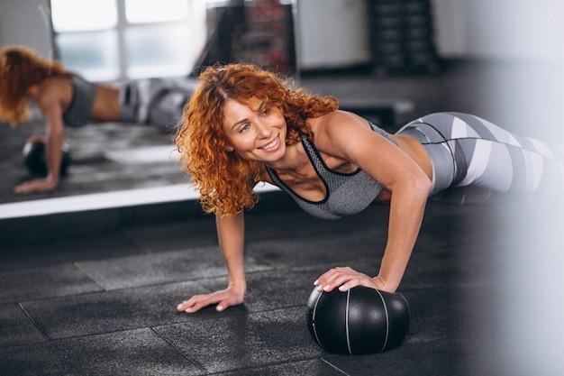 Eignungsfrau, die push-ups an der turnhalle tut