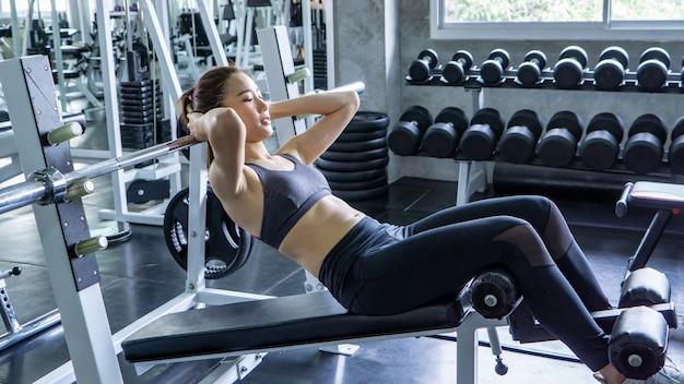 Eignungsfrau, die sit-upsübungen in der turnhalle tut. frau macht abs training