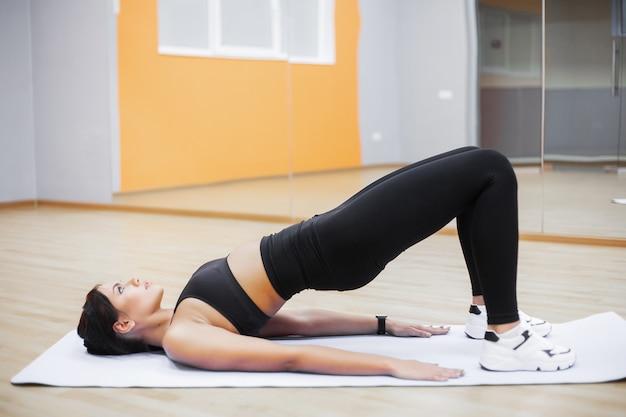 Eignungsfrau, die übungen auf der draufsicht der presse tut. nettes mädchentraining in der turnhalle