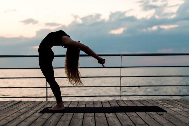Eignungsfrau, die yoga tut und asana nahe dem meer auf sonnenaufgang ausübt