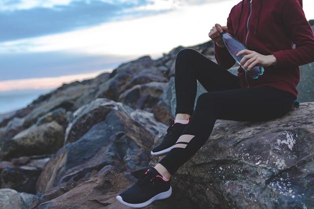 Eignungsfrau in den turnschuhen, die auf einem stein sitzen