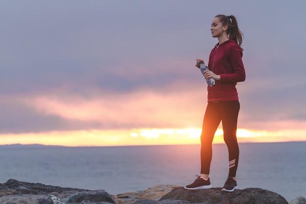Eignungsfrau in den turnschuhen, die auf einem stein stehen, eine flasche wasser halten und den abstand nach einem training auf einem seehintergrund sonnenuntergang untersuchen
