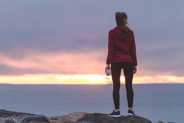 Eignungsfrau in den turnschuhen, die auf einem stein stehen, eine flasche wasser halten und nach einem training auf einem seehintergrund bei sonnenuntergang stillstehen