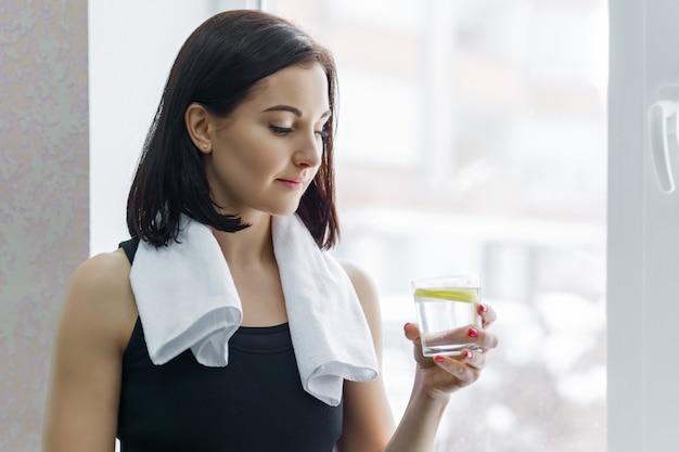 Eignungsfrau in der sportkleidung mit glas wasser und zitrone
