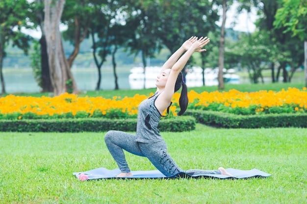 Eignungsfrau in einem park, sie führte yogaübungen durch.