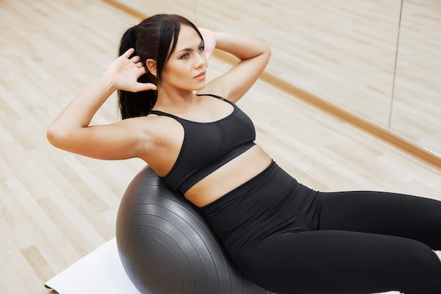 Eignungsfrau, junge attraktive frau, die übungen unter verwendung des balls tut