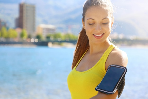 Eignungsfrau mit armband für telefontechnologie, die laufmarathon-übungsjogging macht, das sich am morgen im stadtsee aufwärmt. speicherplatz kopieren.