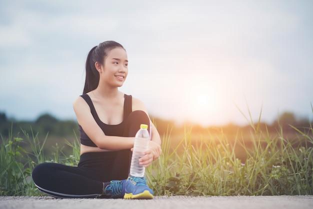 Eignungsfrauenläufer setzen sich hin, entspannend mit wasserflasche, nachdem sie draußen im park ausbilden