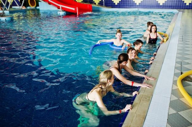 Eignungsgruppe mädchen, die aerobic-übungen im swimmingpool am aquapark tun. sport- und freizeitaktivitäten.