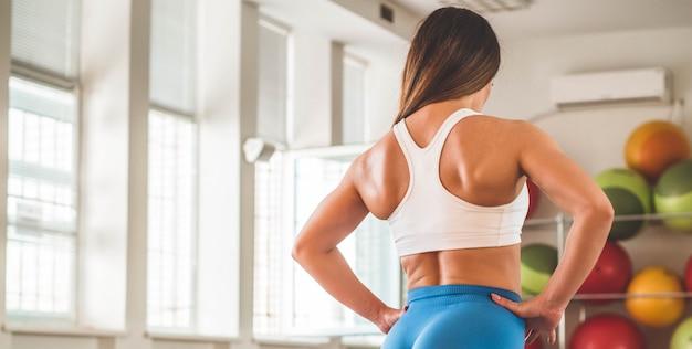 Eignungslehrer im sportraumhintergrund. weibliches model mit muskulöser passform und schlankem körper. sport-konzept