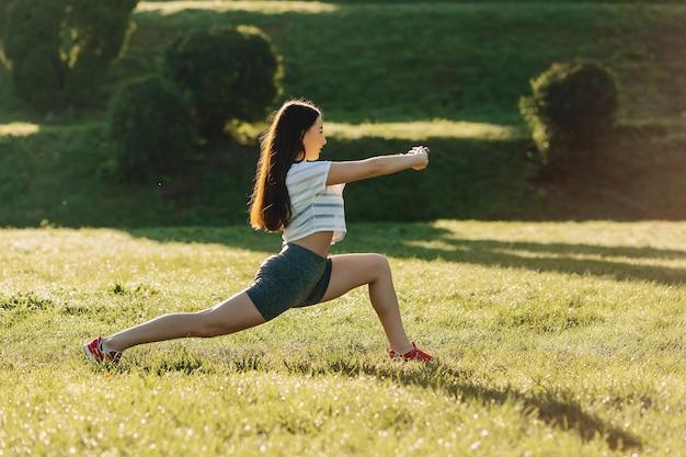 Eignungsmädchen, das draußen ausdehnende übungen auf sonnenschein ein gras macht