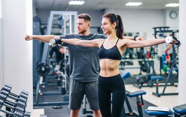 Eignungsmädchen, das gewichtstraining mit unterstützung des trainers in der turnhalle hat.