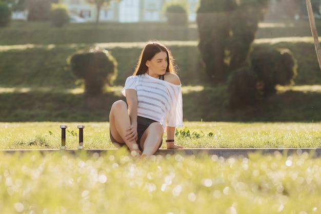 Eignungsmädchen, das übungen mit dummköpfen auf sonnenuntergang am gras draußen macht