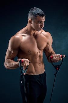 Eignungsmann, der mit dem ausdehnen des bandes trainiert. muskulöser sportmann, der mit elastischem gummiband trainiert. kerl, der mit gummiband ausarbeitet. fit, fitness, bewegung, training und gesunder lebensstil