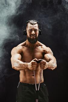 Eignungsmann, der mit dem ausdehnen des bandes trainiert. muskulöser sportmann, der mit elastischem gummiband trainiert.