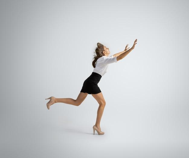 Eile zu neuen zielen. frau in bürokleidung, die auf grauer wand läuft. geschäftsfrau training in bewegung, aktion. ungewöhnlicher look für sport, neue aktivität. sport, gesunder lebensstil.