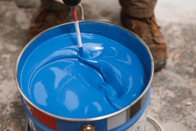 Eimer blaue farbe mischend auf bewegung