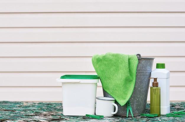 Eimer grüner lappen waschmittel und wäscheklammern auf dem tisch