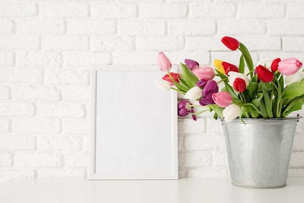 Eimer mit frischen tulpenblumen und leerem rahmen über weißem backsteinmauerhintergrund.