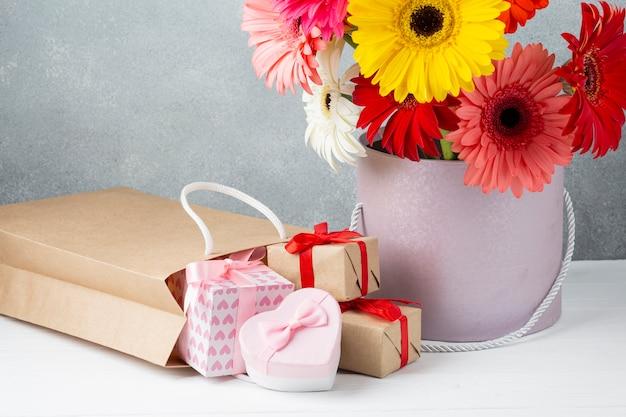 Eimer mit gerberablumen und geschenkpapieren und -kästen