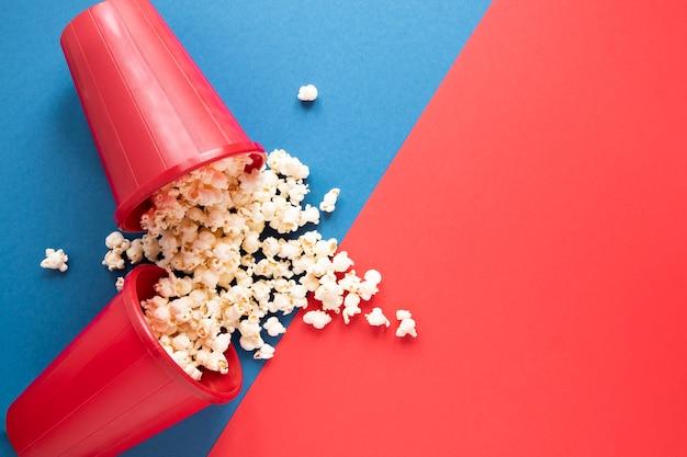 Eimer mit popcorn auf zweifarbigem hintergrund