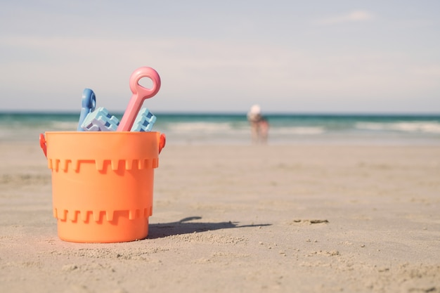 Eimer mit sandspielzeug am strand