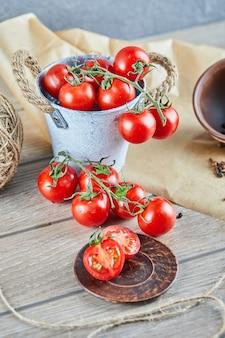 Eimer mit tomaten und halb geschnittenen tomaten auf holztisch.
