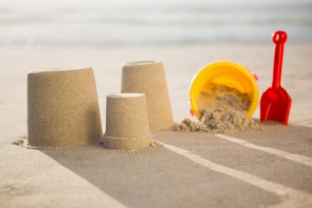 Eimer, schaufel und sandburgen am strand