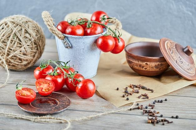 Eimer tomaten und halb geschnittene tomate auf holztisch