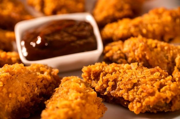 Eimer voll von knusprigem kentucky-brathähnchen mit rauch und barbecue-sauce auf braunem hintergrund. selektiver fokus.