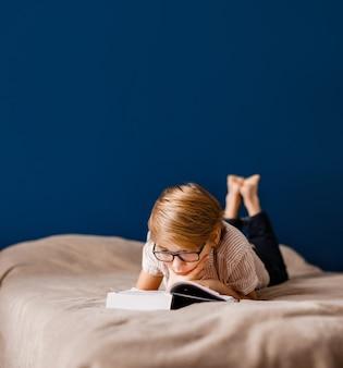 Ein 10-jähriger junge mit brille liegt auf dem bett und liest ein großes buch.