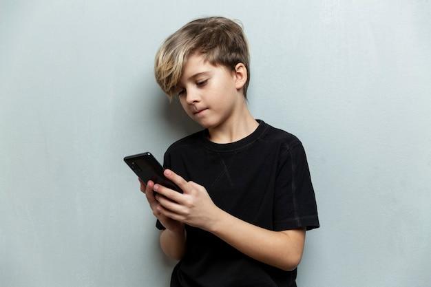 Ein 9-jähriger junge in einem schwarzen t-shirt steht mit einem telefon