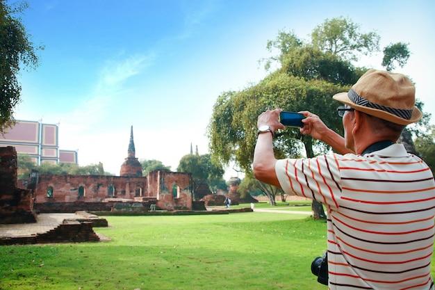 Ein älterer asiatischer mann, der eine kamera an einer archäologischen fundstätte in thailand hält
