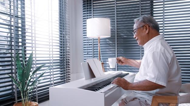 Ein älterer asiatischer mann, der im wohnzimmer seines hauses klavier spielt, nachdem er sich von der arbeit zurückgezogen hat.