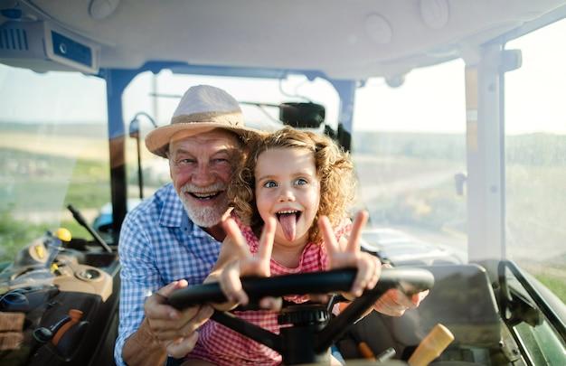 Ein älterer bauer mit kleiner enkelin, die im traktor sitzt und fährt.