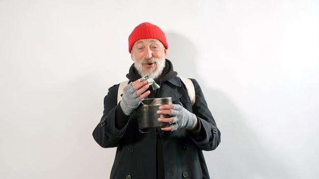 Ein älterer bettler mit einem grauen bart lächelt und hält dollars vor einem isolierten weißen hintergrund